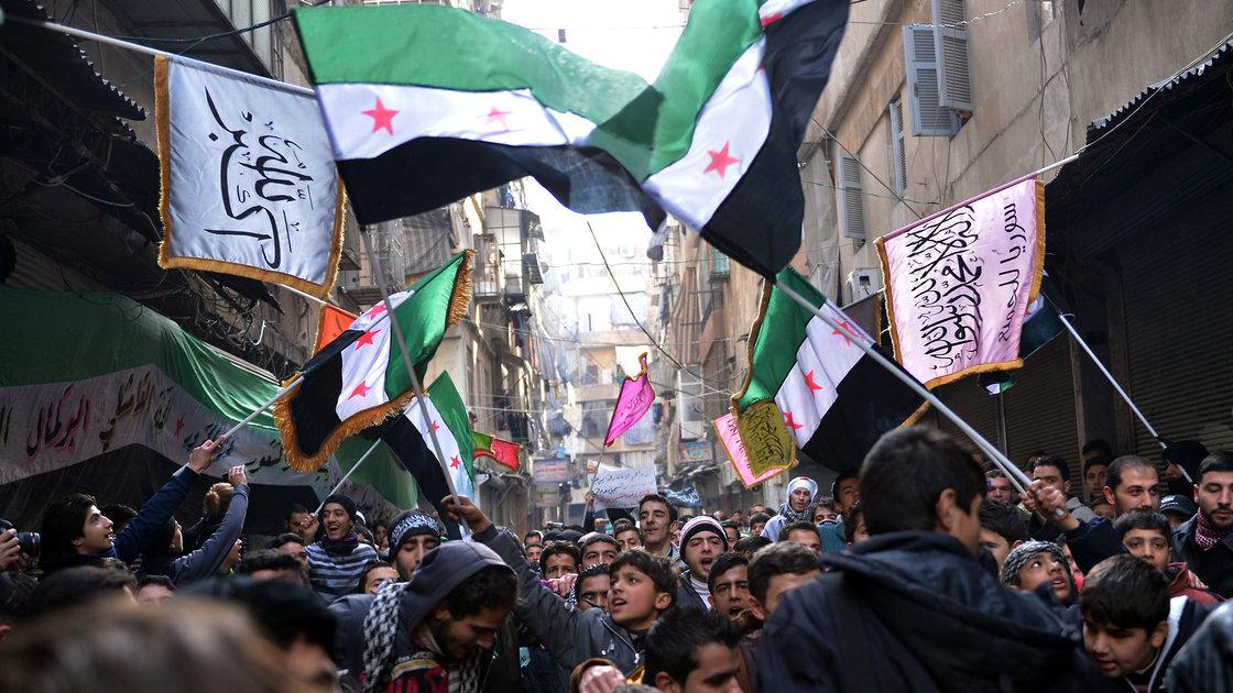 Marcha de rebeldes sirios en Alepo, en 2013. Alzan la antigua bandera siria que hoy los identifica (AFP)